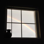 Picture of dark room with bright window and rainbow is seen out window