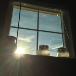 Picture of a window with the sun peeping through and jars sitting on the window