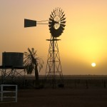 shadowed sunset picture of windmill in desert