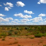 Bright blue sky with fluffy white clouds and red sand and green bushes