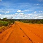 Red sand road with bright blue sky and fluffy white clouds